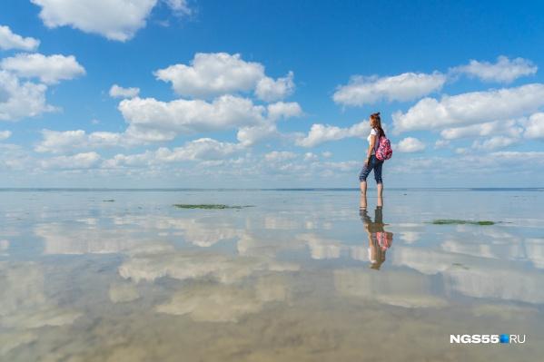 Небо сливается с озером, и облака вместе с людьми копируются в водной глади