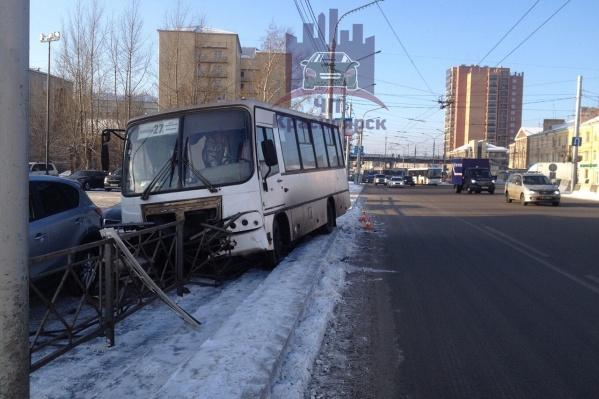Последствия аварии: погнутый забор, две разбитые легковушки и автобус