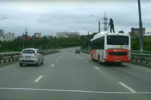Смельчак танцует прямо на крыше движущегося автобуса