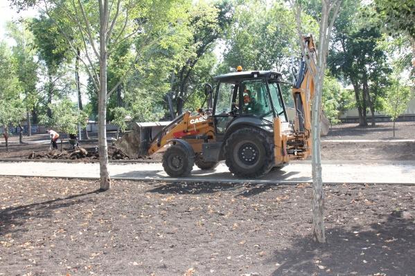 При помощи трактора подрядчик разравнивает землю для высадки газона