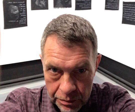Константин Скотников на фоне своих работ