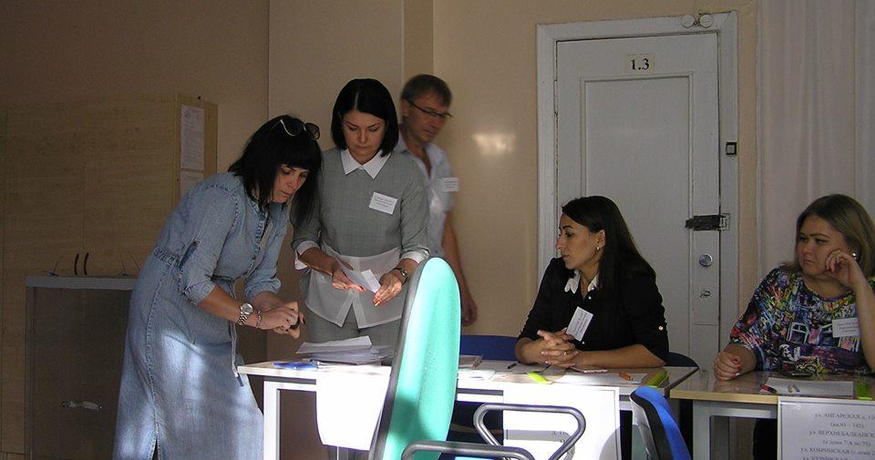 На фото комиссия вскрывает пачку конвертов с досрочными бюллетенями.