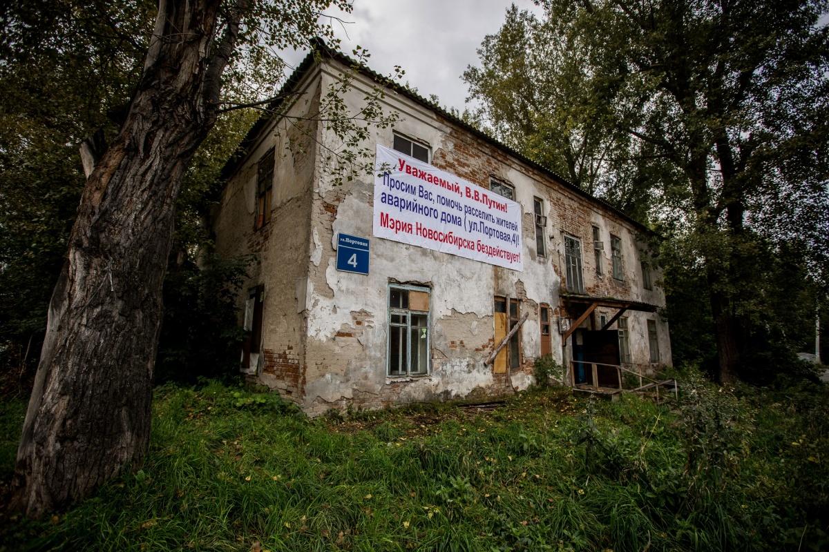 Жильцов заставили снять баннер после репортажа НГС о разваливающемся доме, на стене которого висит обращение к Путину