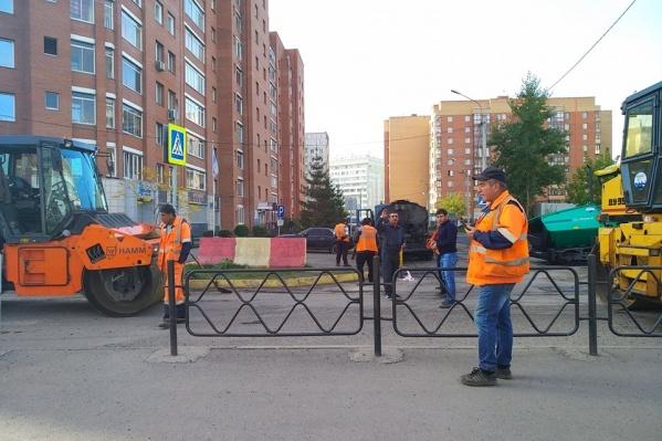 Рабочие убрали шлагбаум, чтобы заасфальтировать дорогу