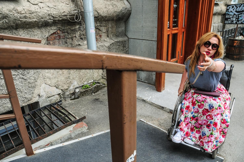 Люди на колясках должны дотянуться до поручней, чтобы забраться на пандус