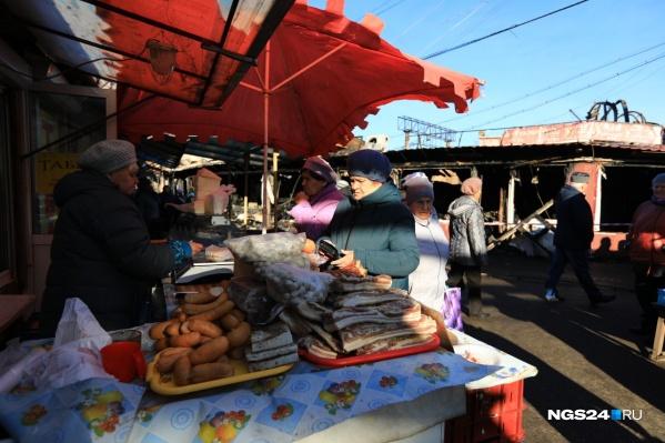 Жизнь на рынке продолжает идти своим чередом рядом с еще теплым пожарищем
