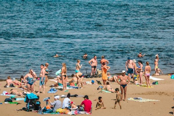 Любители летнего отдыха принимают солнечные ванны и открывают купальный сезон