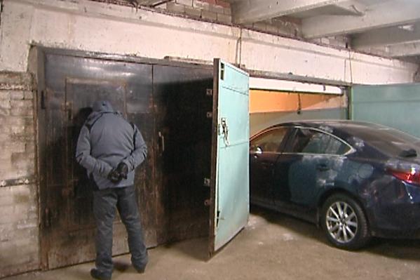 Угонщик рядом с одним из гаражных боксов с угнанным автомобилем