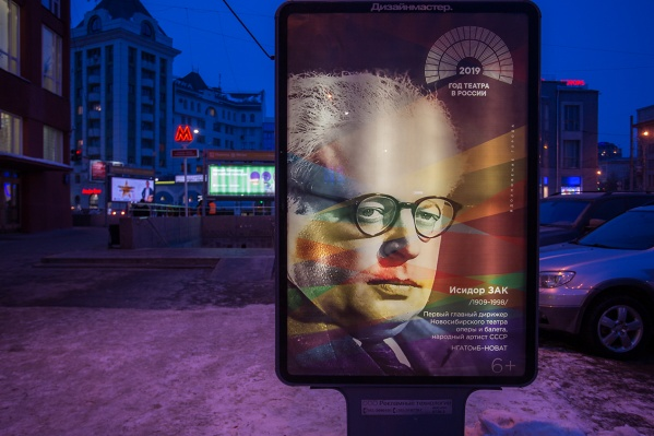 Один из театральных баннеров появился на выходе из метро на станции «Площадь Ленина» возле Госбанка — на нём изображён первый главный дирижёр оперного театра Исидор Зак