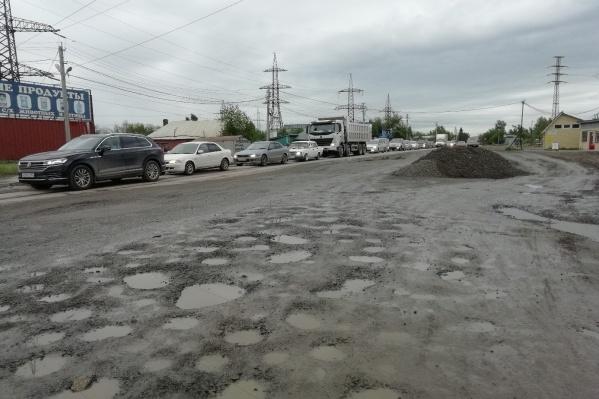 На отремонтированном участке дорожники оставили ямы и гору щебня, ничем их не огородив