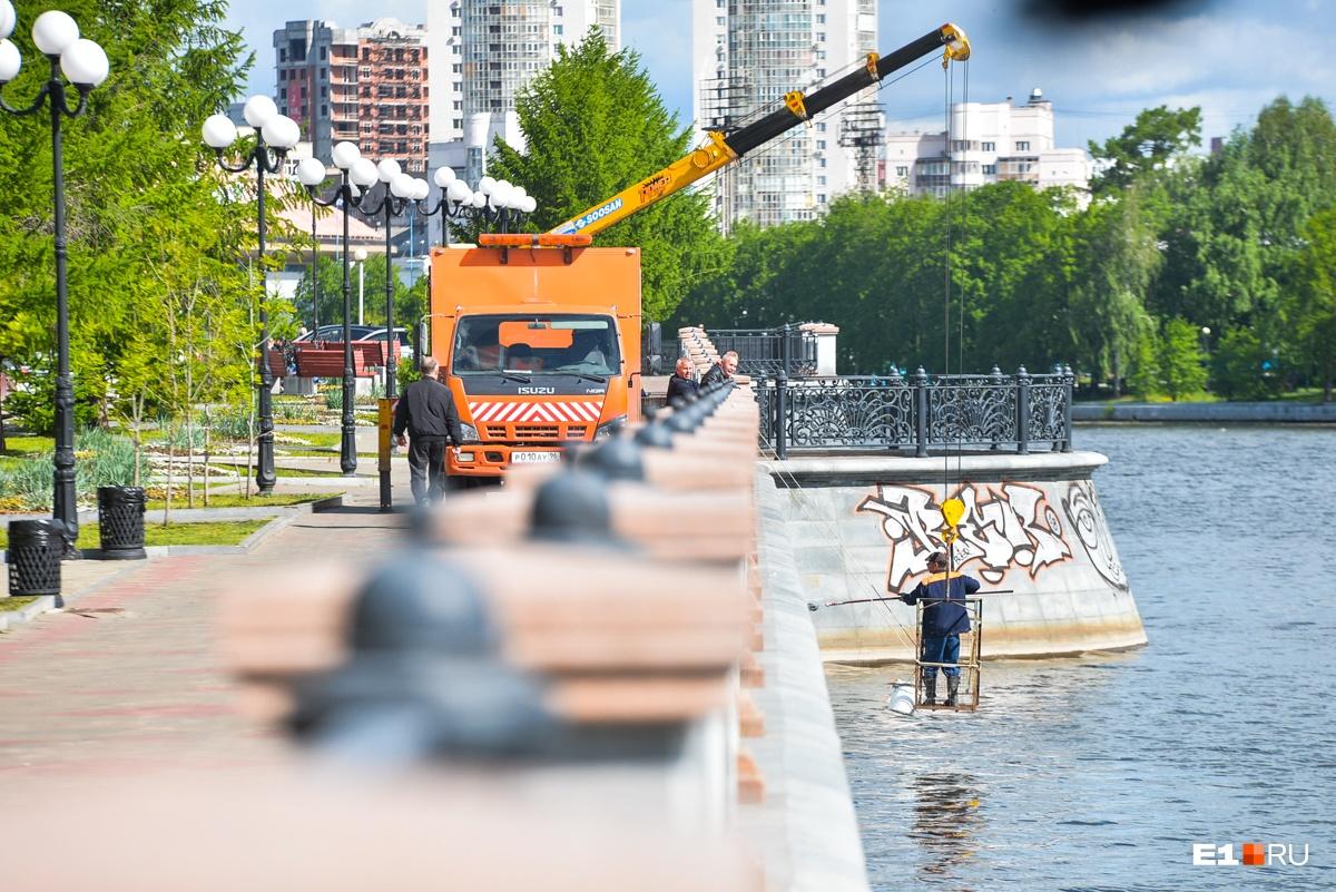 Рабочие экстренно закрашивают краской граффити на гранитной плитке на набережной