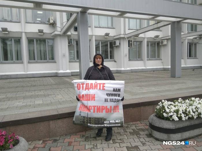 Женщина с плакатом с утра стоит у здания мэрии