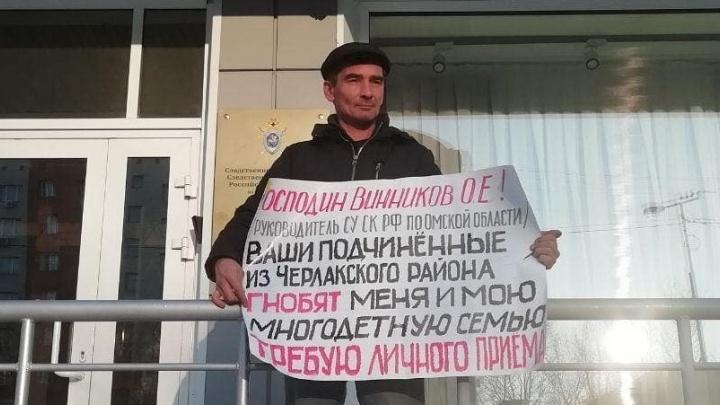 Житель Омской области пришёл к следкому с плакатом и заявил, что его семью «гнобят» силовики