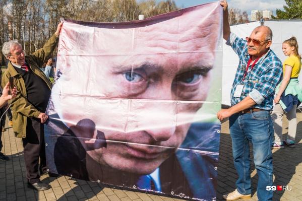 Большой баннер с президентом использовали в качестве подстилки, на которой можно сидеть