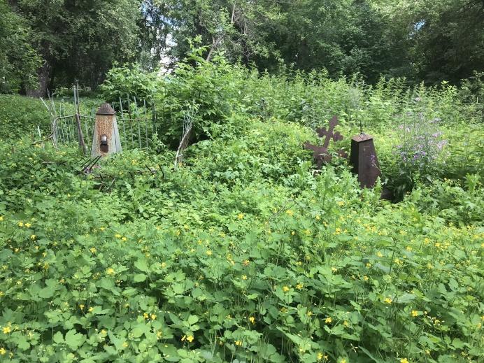 Трава такая высокая, что на некоторых могилах видны только верхушки памятников
