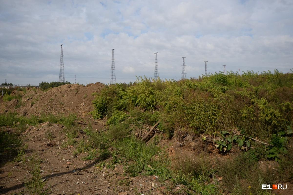 Свежие отвалы грунта. За ними видны далекие антенные поля со стороны Уралмаша