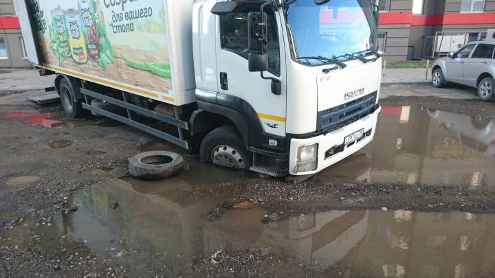 «Полколеса ушло под землю!»: в Самаре грузовик провалился в дыру в асфальте