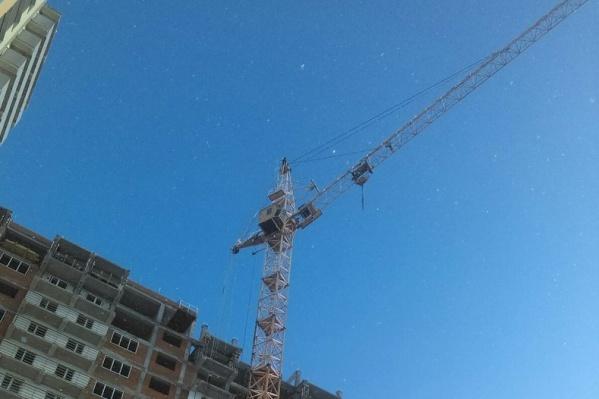 Мужчина залез на кран на строительной площадке дома на улице Беловежской