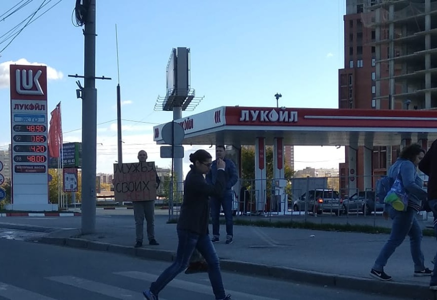 Прохожий стоял с плакатом на тротуаре
