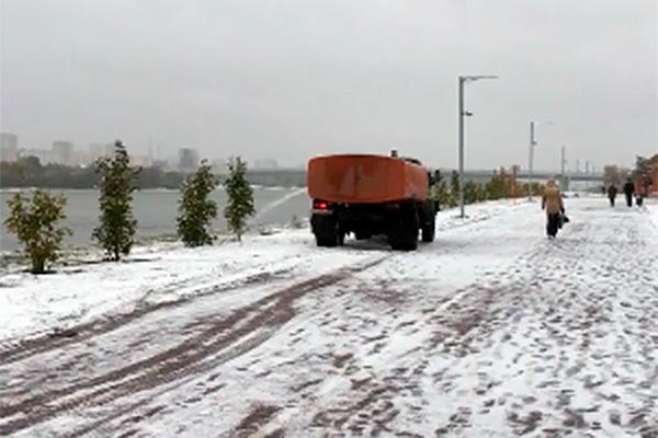 Рабочие полили деревья, припорошенные снегом в Омске