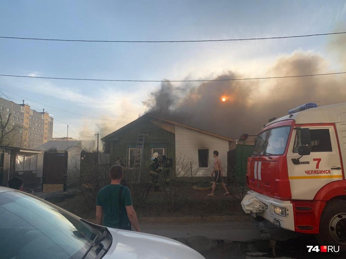 Сгоревший частный дом окружён многоэтажками, жильцы которых высыпали на улицу, увидев дым
