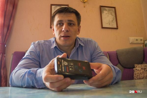 Андрей Боровиков показывает мобильное устройство, которое сообщает полиции, где он находится. Кроме него активист носит на ноге браслет