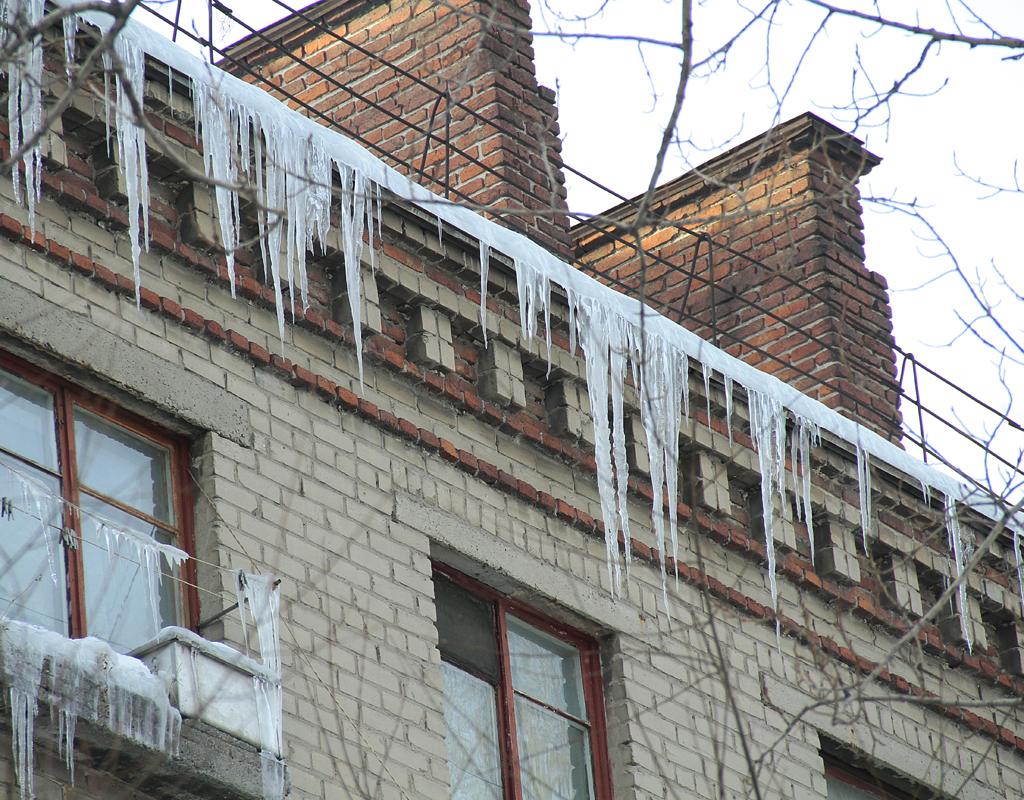 С приходом оттепели на крышах начали расти ледяные сосульки