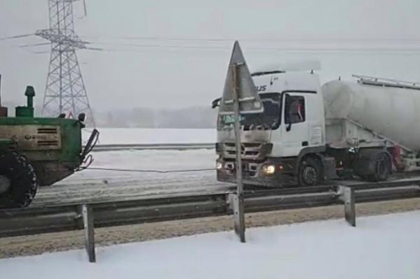 Трактор вызволял из снежного плена грузовики