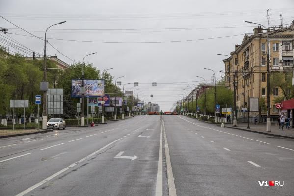 Пасмурный проспект Ленина перегорожен ярко-оранжевыми КАМАЗами муниципальных предприятий