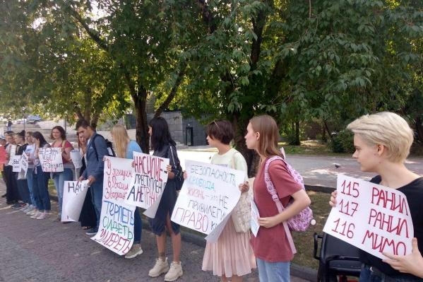 Участники пикета выстроились в линию с самодельными плакатами