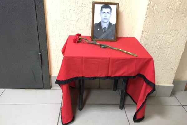 Фото с траурной лентой стоит в коридоре