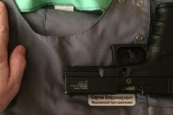 Это фото было опубликовано на «Дваче»: медицинская форма, пистолет и рука