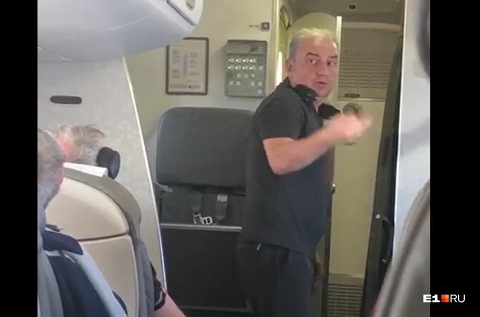 Владимир Шахрин пытается объяснить стюардессе, что на борту невозможно находиться из-за жары