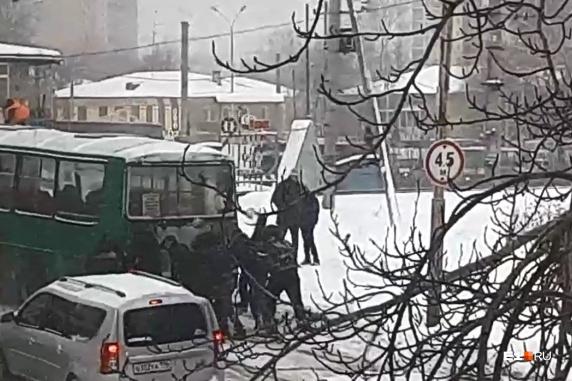 Пассажиры толкают автобус, чтобы преодолеть железнодорожный переезд
