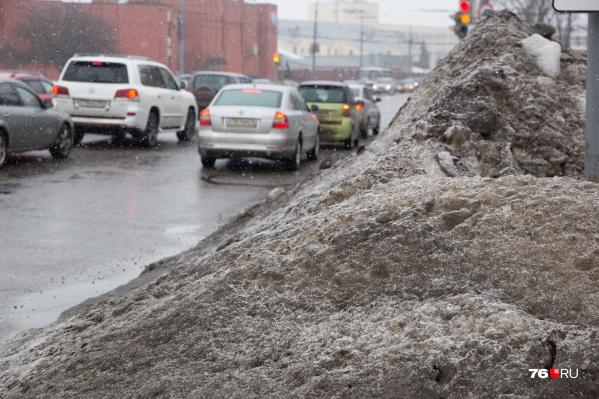 Грязный снег продолжает медленно таять сам, стекая на газоны и тротуары
