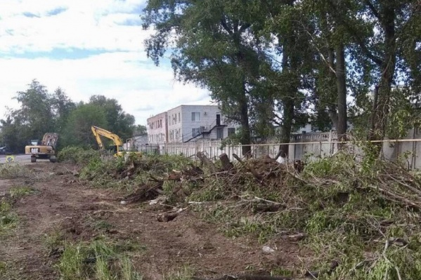 Рабочие очищают место под расширение дороги