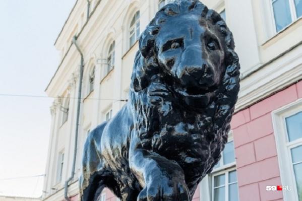 Запоминающееся украшение главного фасада — бдительные львы с шарами
