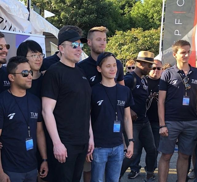 Илон Маск фотографируется с победителями