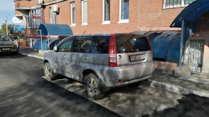 Дорожники рассказали, почему на Омской асфальт уложили вокруг припаркованной машины