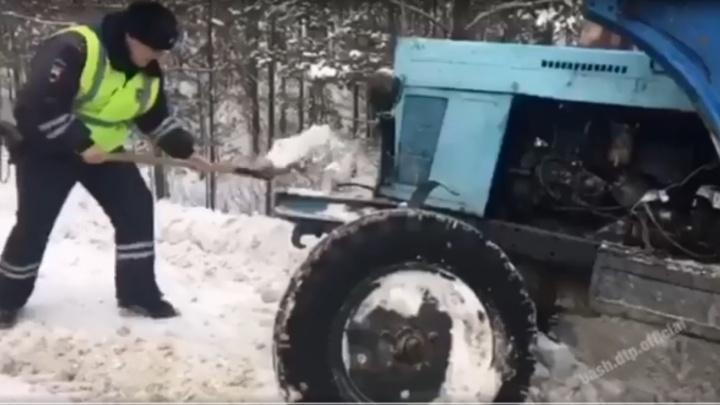 На трассе в Башкирии гаишник расчистил лопатой снег перед застрявшим трактором, видео