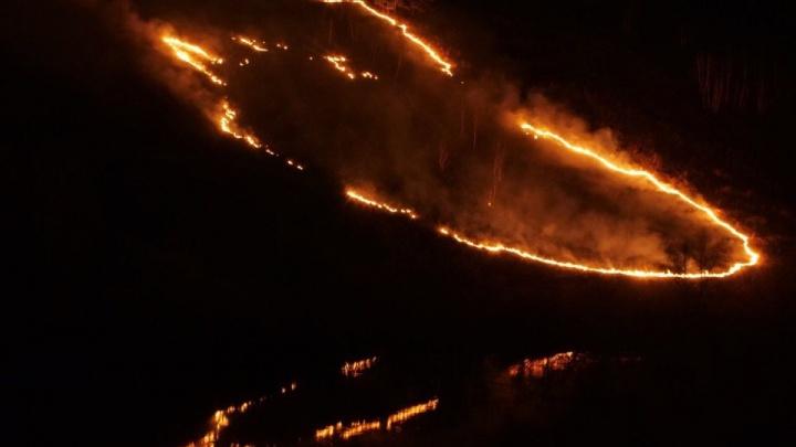 «Апокалиптическое зрелище»: в Октябрьском районе рядом с жилыми домами загорелся склон с травой