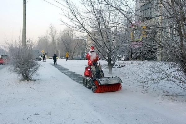 Тротуары чистил рабочий в костюме Деда Мороза