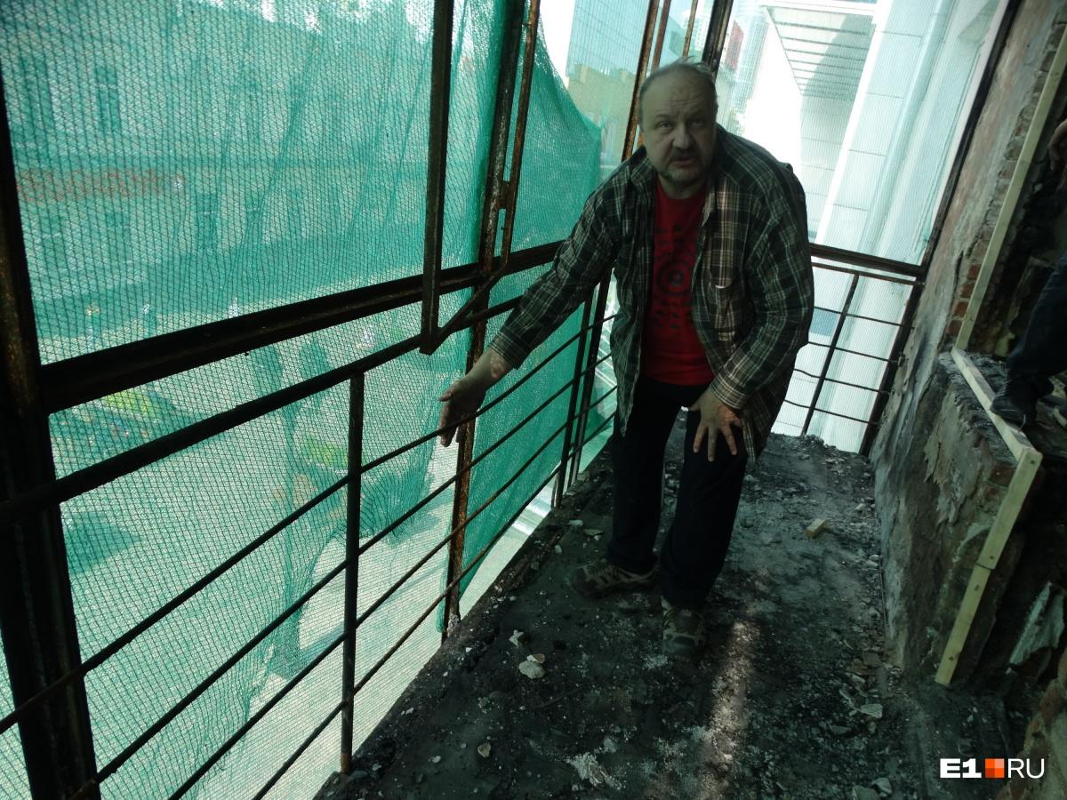 Мужчина показывает, что окурок или какой-то другой горящий предмет мог залететь на его балкон — в пространство между стеклами и ограждением