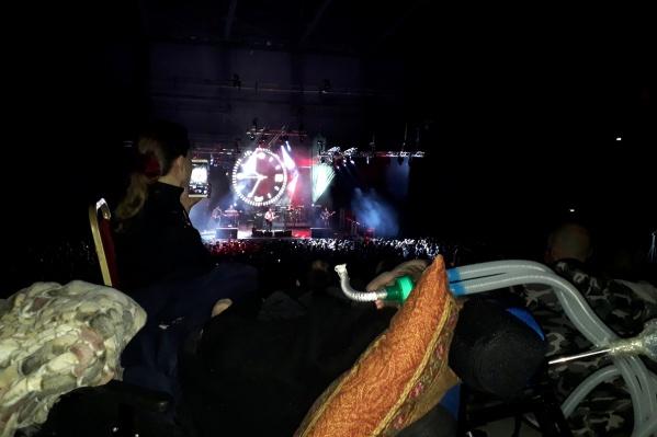 На первом плане — Антон на кресле и трубки, которые помогают ему дышать. На сцене Александр Васильев