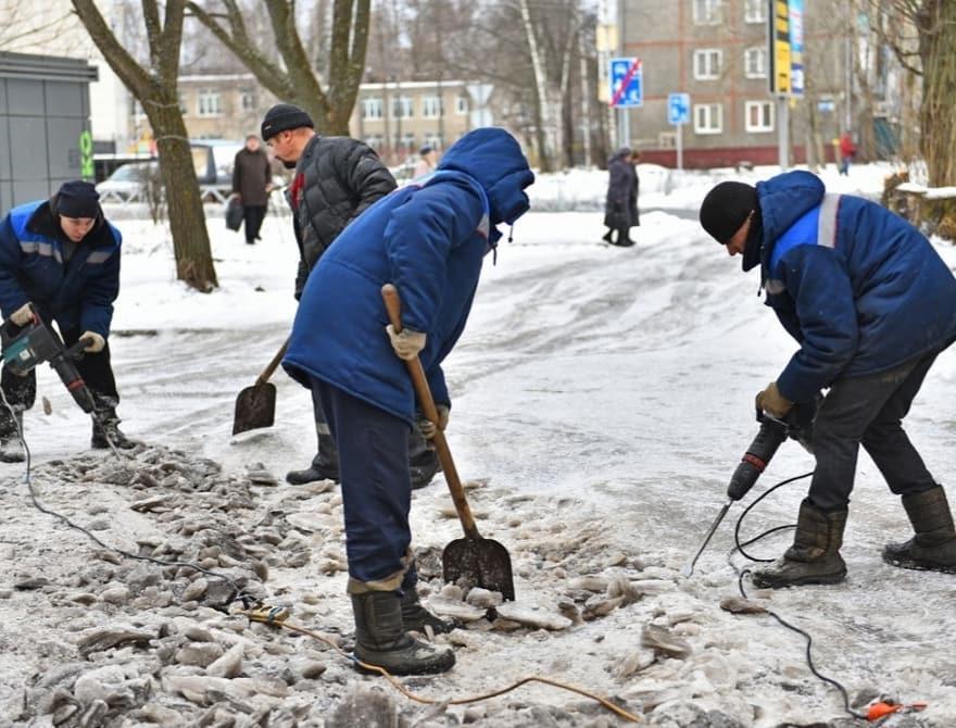 За спинами рабочих видно состояние дороги во льду