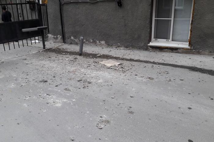 Куски штукатурки падают на тротуар и мешают прохожим во дворе на ул. Ленина