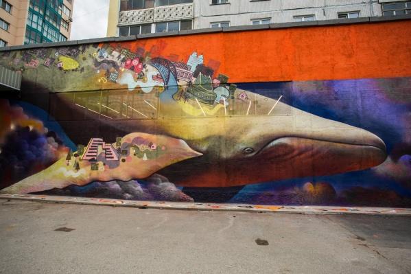 Огромного кита изобразили несущим на спине Новосибирск с его основными достопримечательностями