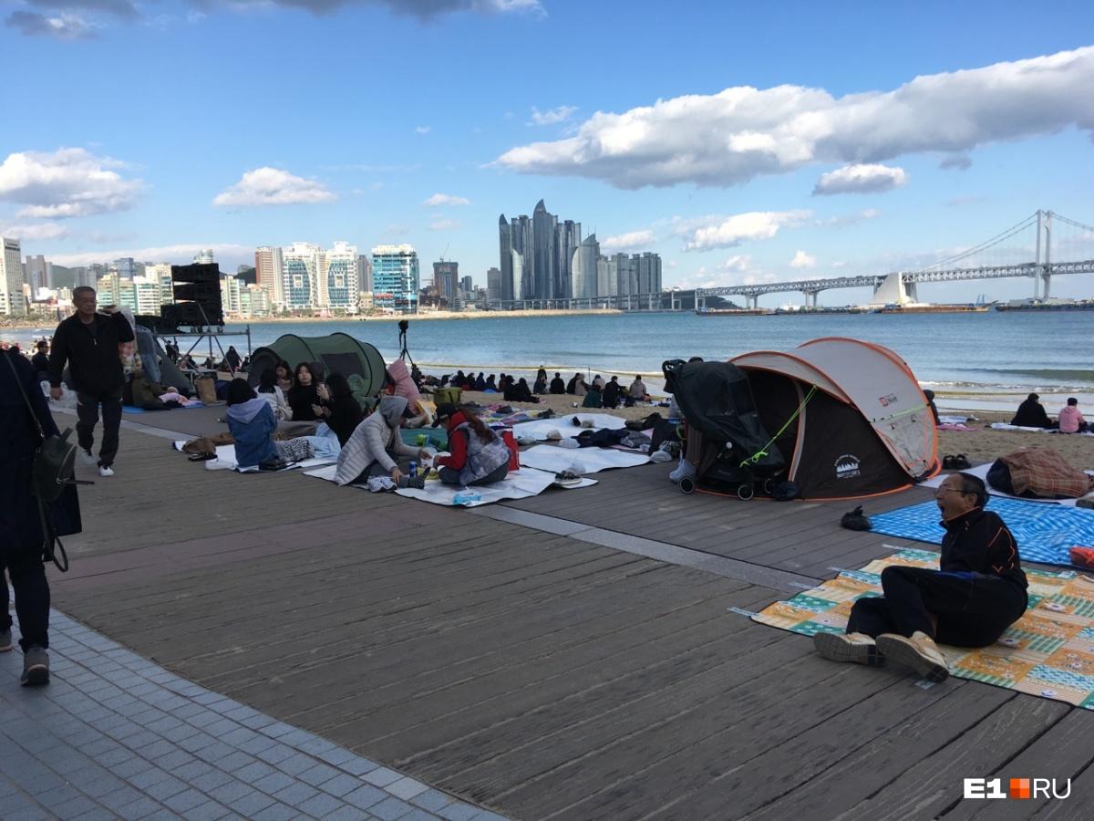 Зрительские места — прямо на пляже, их занимают с утра. Но есть и организованные зоны со стульями (установленными на песке)