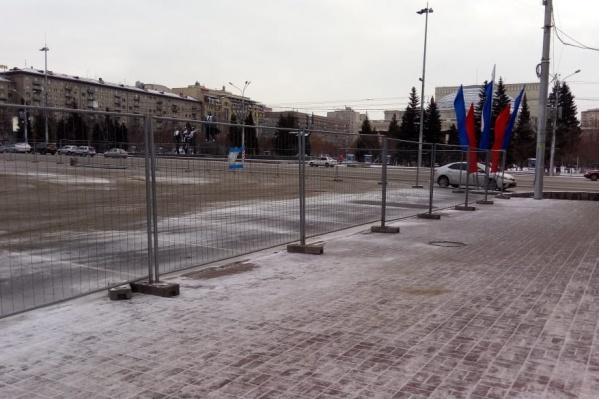На заборе установлены флаги с цветами российского триколора