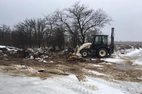 Скопившийся у мемориала мусор убирают тяжелой техникой